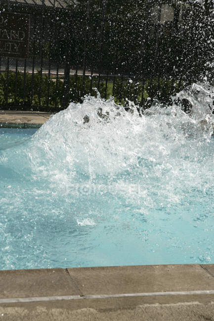 Splashing water in swimming pool on sunny day — Stock Photo