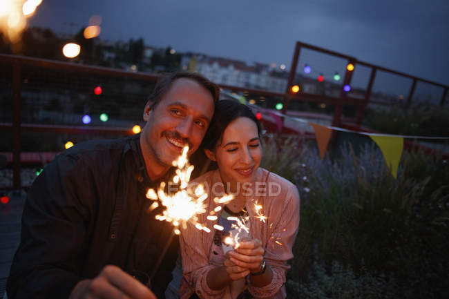 Happy couple holding sparklers on patio at night — Stock Photo