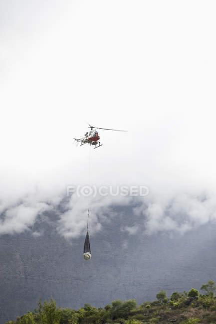 Vista distante de helicóptero transportando suprimentos sobre a terra — Fotografia de Stock