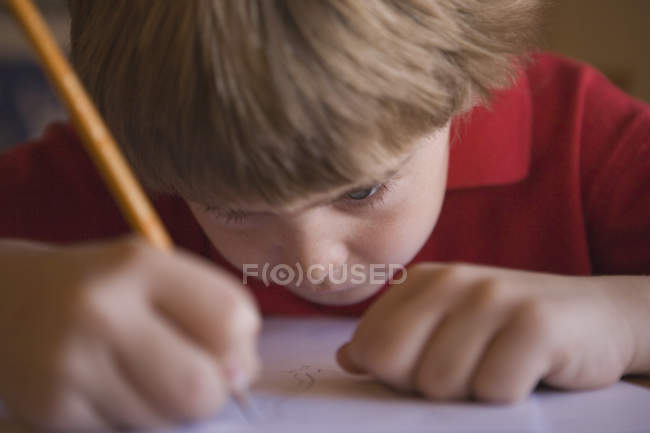 Young boy writing indoors — Stock Photo