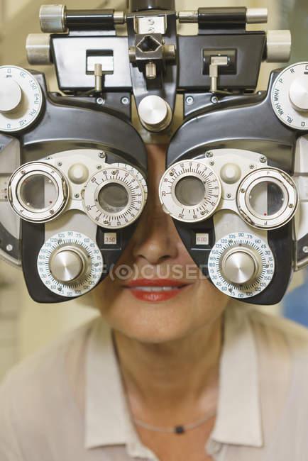 Smiling senior woman getting vision examination at clinic — Stock Photo