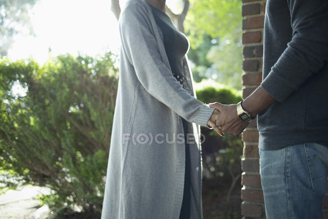 Midsection of couple holding hands against plants — Stock Photo