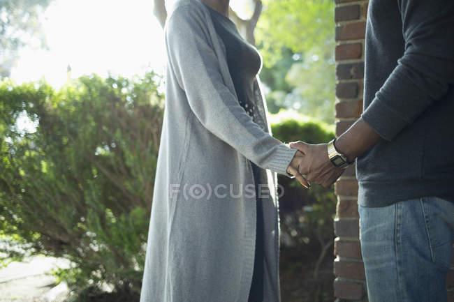 Середина пары, держащейся за руки против растений — стоковое фото