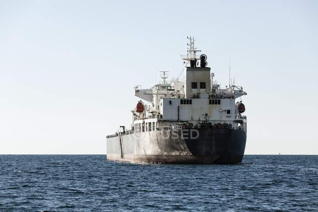 Buque de carga moviéndose sobre el mar contra el cielo - foto de stock
