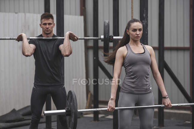 Confident female and male athletes exercising with barbells during crossfit training — Stock Photo