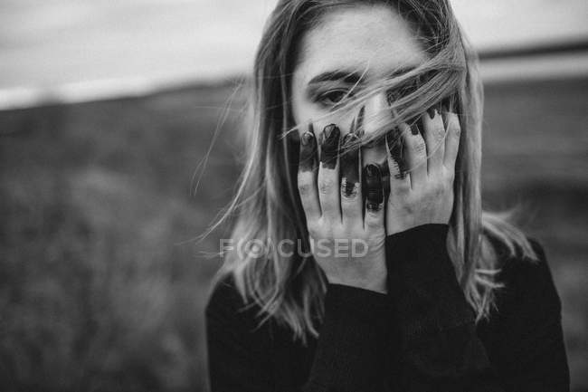 Portrait of teenage girl with messy hands covering face on field — Stock Photo