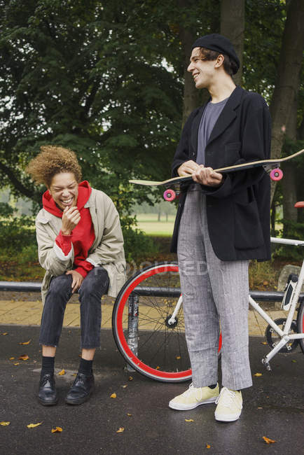 Happy friends with bicycle and skateboard having fun in park — Stock Photo