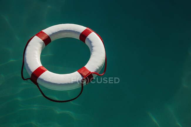 Vista ad alto angolo di anello di vita bianca galleggiante sul mare — Foto stock