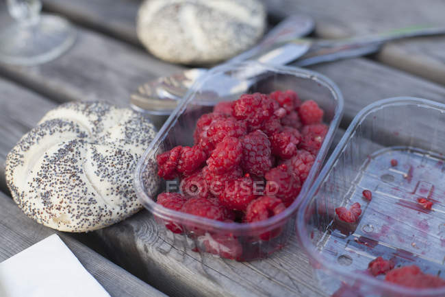 Close up view of raspberries in container by bread roll on table — Stock Photo