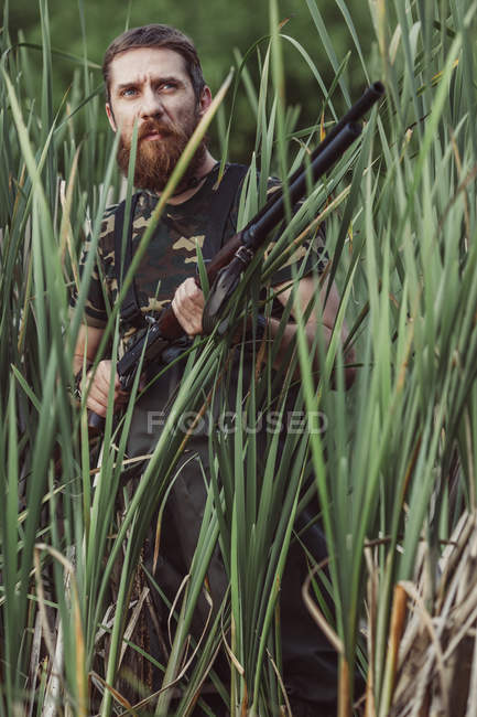 Hunter looking away while standing on grassy field — Stock Photo