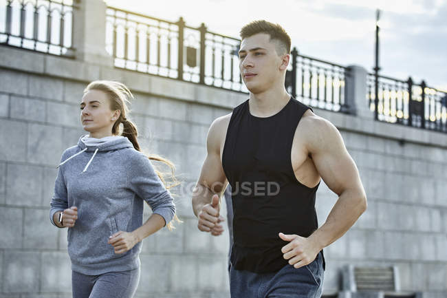 Young male and female athletes jogging against wall — Stock Photo