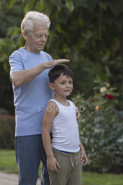 Smiling grandfather measuring grandsons height while standing at park — Stock Photo