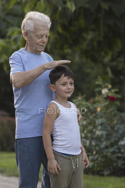 Sonriente abuelo medición altura de nietos estando en el Parque - foto de stock
