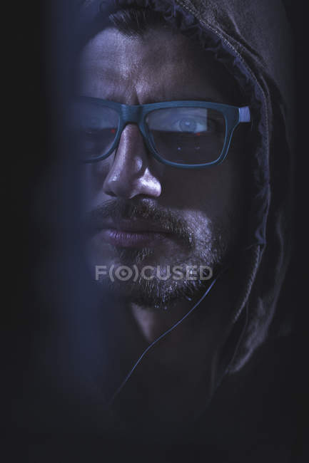 Close-up of serious man wearing eyeglasses and hood — Stock Photo