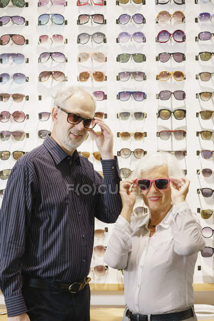 Portrait of smiling man and woman wearing sunglasses while standing in store — Stock Photo