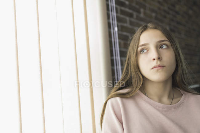 Thoughtful Teenage girl sitting at curtain at home — Stock Photo
