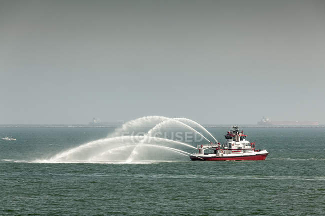 Fire boat spraying water into sea against sky — Stock Photo