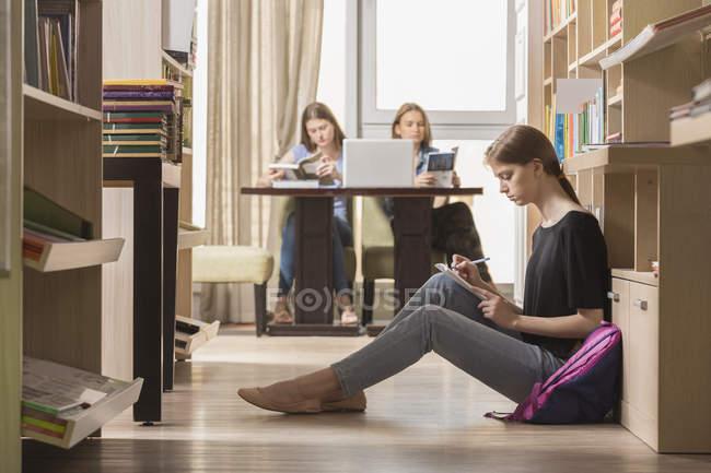 Estudiantes serios en biblioteca - foto de stock