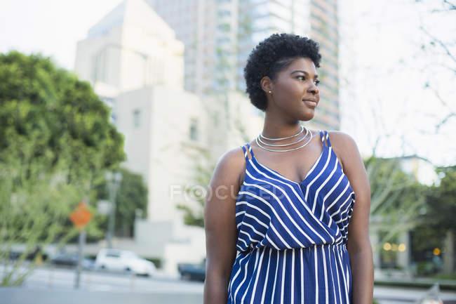 Frau in blau gestreiftem Kleid steht gegen Gebäude in der Stadt — Stockfoto