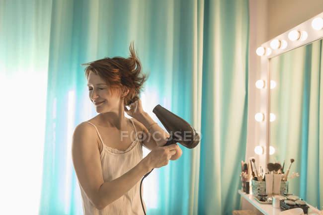 Sorrindo mulher de pé na frente do espelho na mesa de vestir — Fotografia de Stock