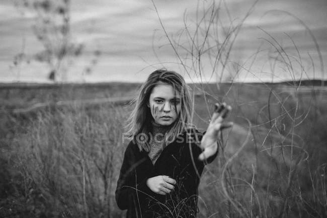 Portrait of teenage girl with messy face standing at dried plants on field — Stock Photo