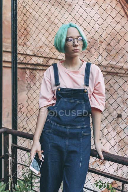 Ragazza adolescente in possesso di telefono cellulare mentre in piedi alla recinzione in città — Foto stock