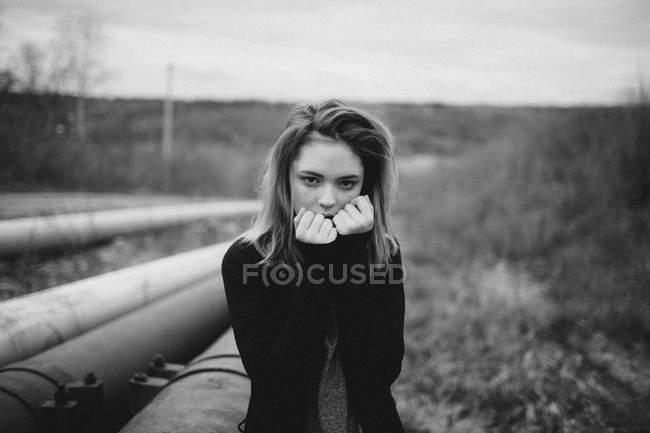 Retrato de adolescente grave em pé ao lado de tubos em campo — Fotografia de Stock