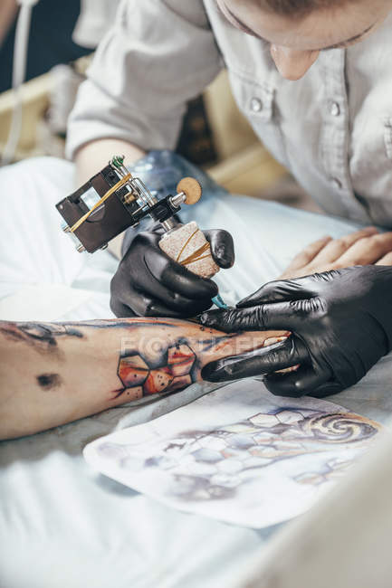 Concentré d'artiste de tatouage de conception sur la main de l'homme — Photo de stock