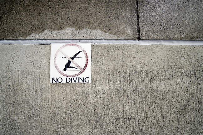 Stone wall with prohibition sign with no diving inscription — Stock Photo