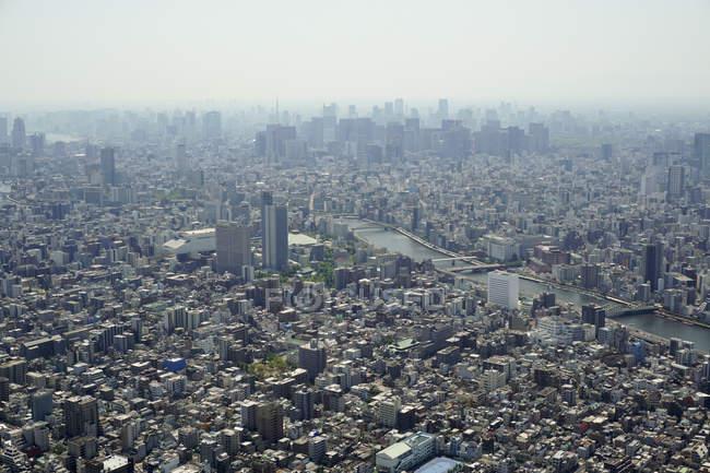 Vista aérea da paisagem urbana lotada contra o céu no dia ensolarado — Fotografia de Stock