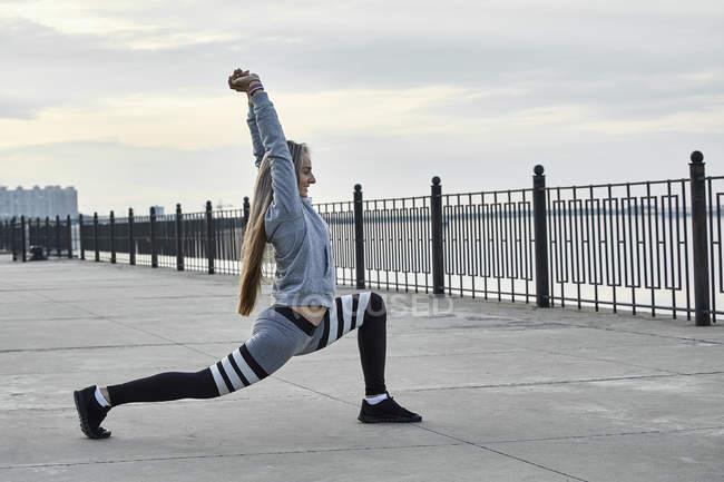 Atleta feminina que se estende no calçadão no lago — Fotografia de Stock