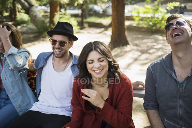 Allegro maschio e femmina amici seduti sulla panchina nel parco — Foto stock