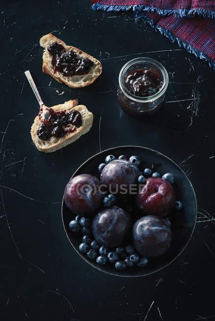 Tiro directamente encima de las frutas en un tazón con bocadillos en la superficie de granito - foto de stock
