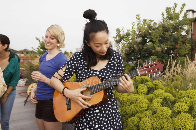 Woman playing guitar on patio while female friends standing on background — Stock Photo