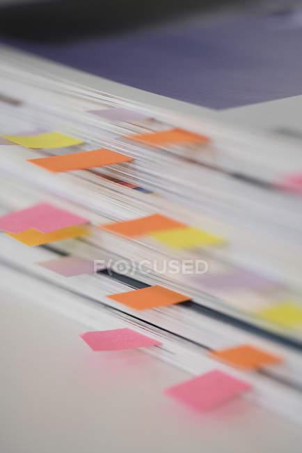 Cerrar vista de libros apilados con coloridos marcadores de mesa - foto de stock