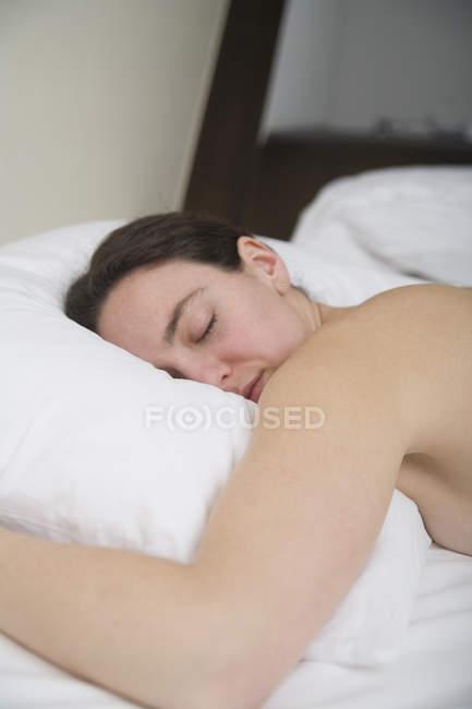 Frau mit braunen Haaren liegt vorne im Bett — Stockfoto