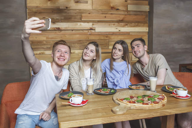 Young friends taking selfie while sitting in restaurant — Stock Photo