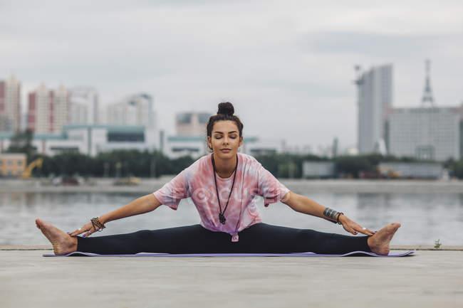 Красивая женщина практикует йогу против реки в городе — стоковое фото