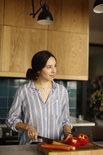 Mulher olhando para longe enquanto cortar cenoura na ilha de cozinha — Fotografia de Stock
