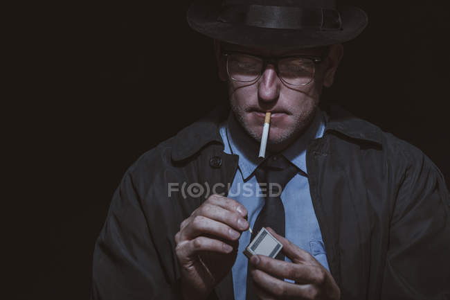 Young man lighting matchstick against black background — Stock Photo
