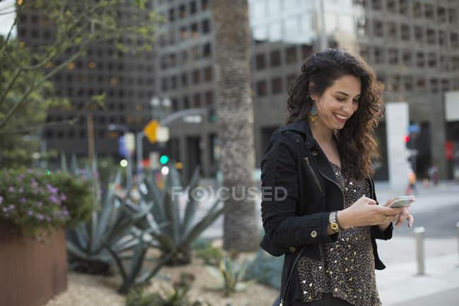 Змеиная женщина с помощью мобильного телефона против зданий в городе, Лос-Анджелес, Калифорния, США — стоковое фото