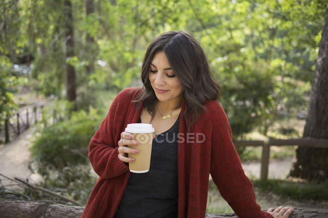 Mid adult woman holding disposable glass while standing in park — Stock Photo