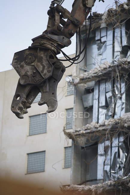 Низький кут зору кран проти знесеного структури на будмайданчик — стокове фото