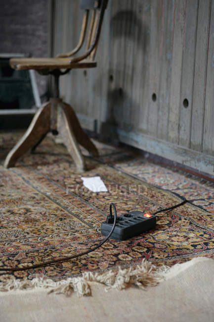 Electrical extension cord on ornate carpet — Stock Photo