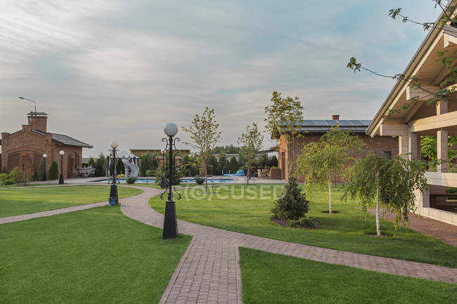 Electric lights by footpath on lawn in back yard against sky — Stock Photo