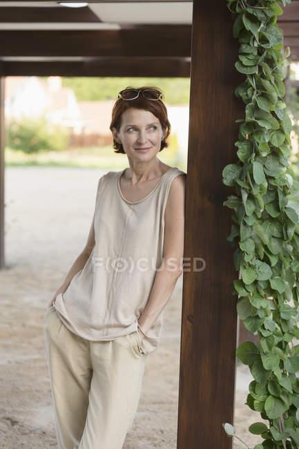 Задумчивая женщина опирается на деревянную колонну в парке — стоковое фото