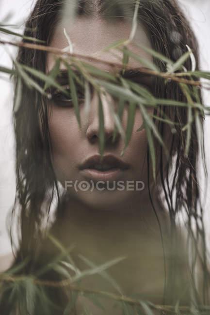 Gros plan de femme avec les cheveux mouillés, regardant à travers les branches — Photo de stock