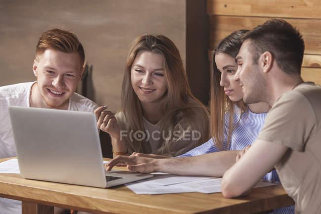 Молодий друзі, використовуючи ноутбук сидячи в ресторані — стокове фото