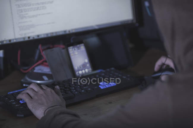 Cropped image of computer hacker with smart phone at table — Stock Photo