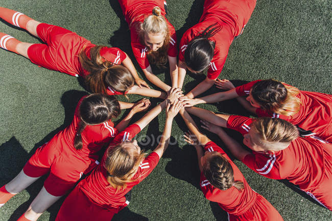 High angle view of sports team stacking hands on field — Stock Photo